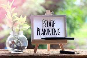 """small sign on an easel with the words """"estate planning"""" on it"""